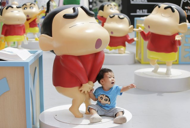 A boy sits next to a Crayon Shin-chan model during an exhibition at Joy City in Beijing May 5, 2015. (Photo by Jason Lee/Reuters)
