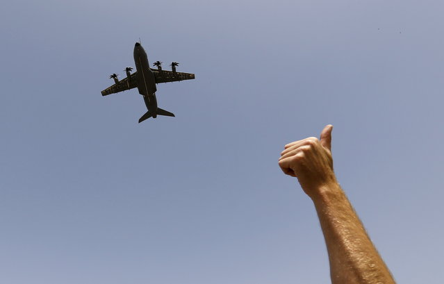 An Airbus A400M military plane flies before landing as a man gives a thumbs-up sign during a test flight at the airport of the Andalusian capital of Seville May 12, 2015. Airbus carried out a test flight of one of its A400M military transporters on Tuesday, as it tried to restore confidence after a fatal crash on Saturday. (Photo by Marcelo del Pozo/Reuters)
