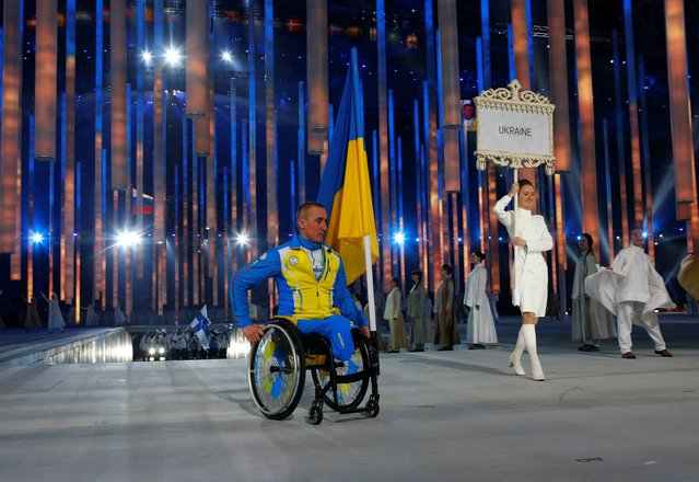 Biathlete Mykhaylo Tkachenko, representing Ukraine, enters the arena during the opening ceremony of the 2014 Winter Paralympics at the Fisht Olympic stadium  in Sochi, Russia, Friday, March 7, 2014. (Photo by Dmitry Lovetsky/AP Photo)
