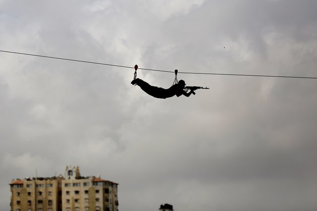 A member of the Palestinian Hamas security forces decends down a zip-line during their military training graduation ceremony in Gaza City on May 21, 2015. (Photo by Mohammed Abed/AFP Photo)