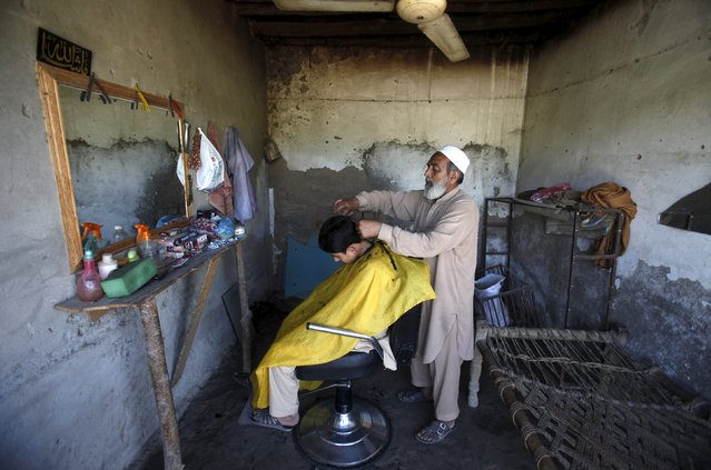 A boy gets his hair cut in a barber shop in Charsadda near Peshawar April 8, 2015. (Photo by Fayaz Aziz/Reuters)