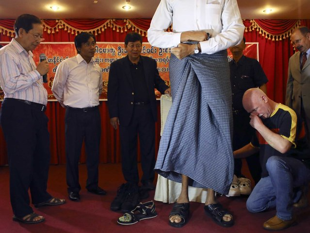 German shoemaker Georg Wessels (R) presents shoes to Win Zaw Oo, who according to his medical team, at 2.3 metres (7.5 ft), is Myanmar's tallest man, in Yangon March 26, 2014. (Photo by Reuters/Minzayar)