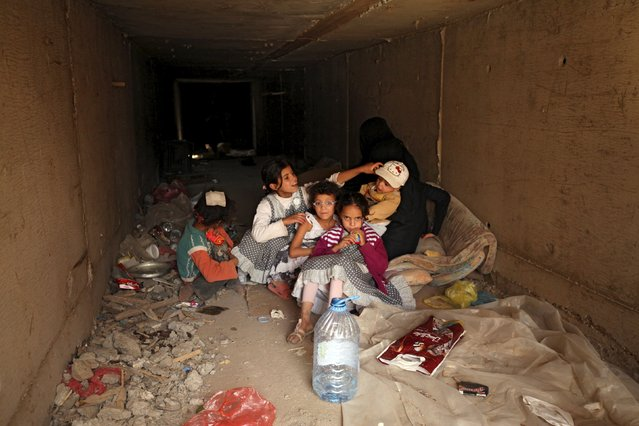 A family rest in an underground water tunnel with other displaced Yemeni families (not pictured), after they were forced to flee their home due to ongoing air-strikes carried out by the Saudi-led coalition in Sanaa May 2, 2015. (Photo by Mohamed al-Sayaghi/Reuters)