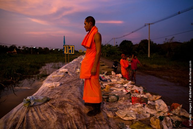 A Thai Dhammakaya monk takes a rest from working to fortify the flood gate he stands on, as he looks out over the rising flood waters at Khlong Rapi Pat