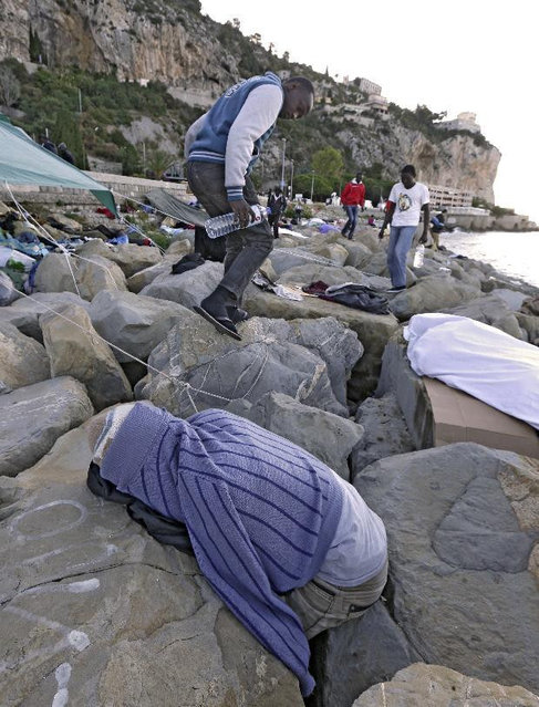 A migrant walks by others sleeping on the rocky beach at the Franco-Italian border near Menton, southeastern France Wednesday, June 17, 2015. European Union nations failed to bridge differences Tuesday over an emergency plan to share the burden of the thousands of refugees crossing the Mediterranean Sea, while on the French-Italian border, police in riot gear forcibly removed dozens of migrants. (AP Photo/Lionel Cironneau)
