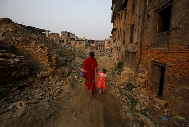 A woman and a child walk past the remains of collapsed houses damaged during the April 2015 earthquake, in Bhaktapur, Nepal March 18, 2016. The two devastating earthquakes that struck Nepal last year killed almost 9,000 people across the country. Inside the Kathmandu Valley almost 2,000 died, and some of the area's most important cultural and heritage sites were completely destroyed. As Kathmandu inhabitants prepare to mark the one-year anniversary of the event, thousands are still displaced and millions are living in temporary shelters. (Photo by Navesh Chitrakar/Reuters)