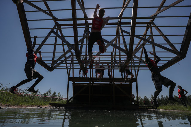 Men compete in a Hero Race extreme cross-country obstacle course racing event at the Sviyaga Hills resort in Kazan, Russia on June 8, 2019. (Photo by Yegor Aleyev/TASS)