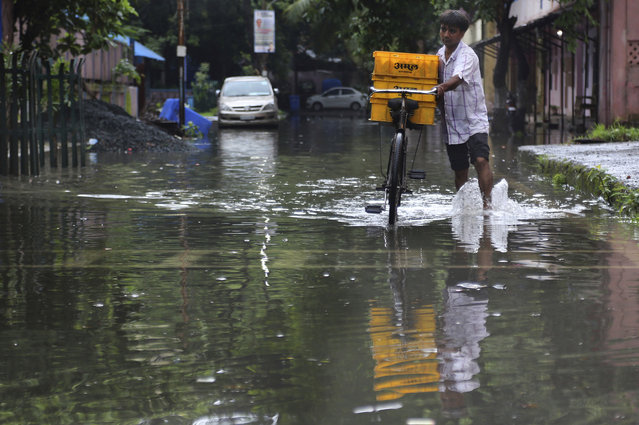 A man pushes his bicycle, carrying milk for sale, past a waterlogged street after rainfall in Mumbai, India, Wednesday, July 24, 2019. India's monsoon season runs from June to September. (Photo by Rafiq Maqbool/AP Photo)