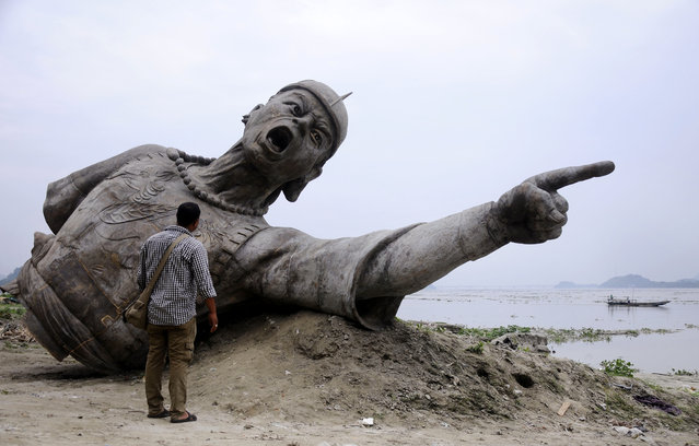 An Indian bystander looks at a part of a bronze statue of Lachit Borphukan, which is set to be installed in the middle of the River Brahmaputra, in Guwahati on May 21, 2015. Lachit Borphukan was a commander in the Ahom kingdom known for his leadership in the 1671 Battle of Saraighat that thwarted a drawn-out attempt by Mughal forces. (Photo by AFP Photo/Stringer)
