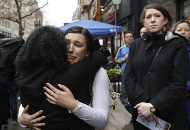 Olivia Savarino, center, hugs Christelle Pierre-Louis, left, as Callie Benjamin, right, looks on near the finish line of the Boston Marathon during ceremonies on Boylston Street, Tuesday, April 15, 2014, in Boston. Savarino and Benjamin were working at the Forum restaurant when a bomb went off in front of the building on April 15, 2013. (Photo by Steven Senne/AP Photo)