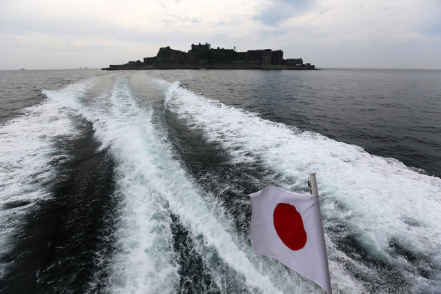 "In this June 29, 2015 photo, a Japanese flag is hoisted on a tourist boat as Hashima Island, commonly known as Gunkanjima, which means ""Battleship Island"", is seen off Nagasaki, Nagasaki Prefecture, southern Japan. (Photo by Eugene Hoshiko/AP Photo)"