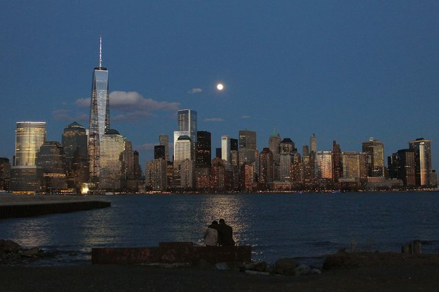 The moon rises behind the skyline of New York's Lower Manhattan as two people watch from a park along the Hudson River in Jersey City. (Photo by Gary Hershorn/Reuters)