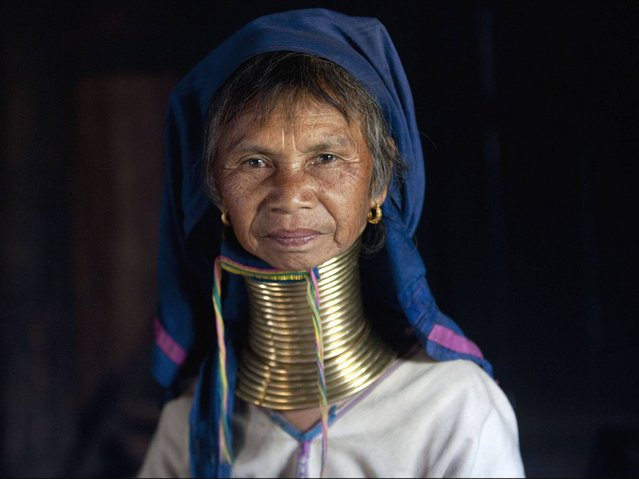 """Women of the Kayan tribes identify themselves by their forms of dress. Women of the Kayan Lahwi tribe are well known for wearing neck rings, brass coils that are placed around the neck, appearing to lengthen it. The women wearing these coils are known as """"giraffe women"""" to tourists. (Photo by Ye Aung Thu/AFP Photo)"""