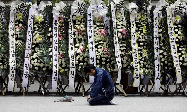 A mourner pays tribute to the victims of the sunken ferry Sewol near condolence flowers during a temporary memorial at the auditorium of the Olympic Memorial Museum in Ansan, south of Seoul, South Korea, Thursday, April 24, 2014. Divers made their way deeper Thursday into the submerged wreck of a ferry that sank more than a week ago as the death toll neared 160 and relatives of the more than 140 still missing pressed the government to finish the grim task of recovery soon. (Photo by Lee Jin-man/AP Photo)