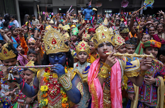 Children dressed up as Hindu Lord Krishna attend Janmashtami, or the birth anniversary of Lord Krishna, festival celebrations inside a school in Ahmedabad, India, August 23, 2019. (Photo by Amit Dave/Reuters)