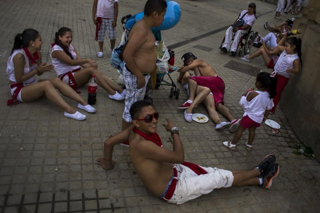 A couple play as they have lunch with friends on the street to celebrate the official opening of the 2015 San Fermin fiestas in Pamplona, Spain, Monday, July 6, 2015. (Photo by Andres Kudacki/AP Photo)