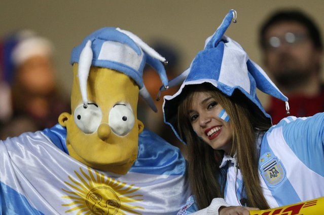 Supporters of Argentina, one of them dressed as cartoon character Homer Simpson, pose for photos on the stands before a Copa America semifinal soccer match between Argentina and Paraguay at the Ester Roa Rebolledo Stadium in Concepcion, Chile, Tuesday, June 30, 2015. (Photo by Andre Penner/AP Photo)
