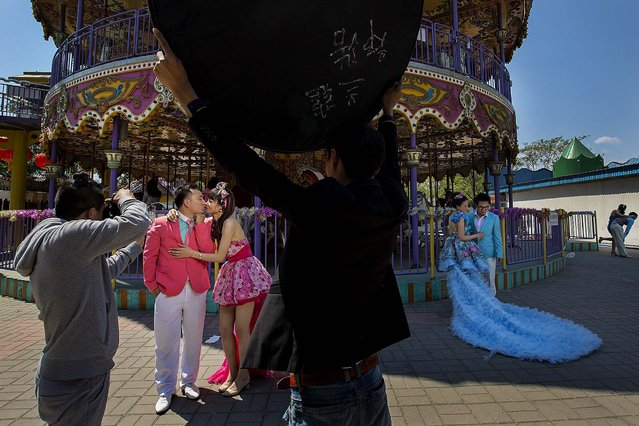 Newlyweds pose for photos near a carousel at a park during China's national May Day holidays in Beijing, on May 2, 2014. (Photo by Alexander F. Yuan/Associated Press)