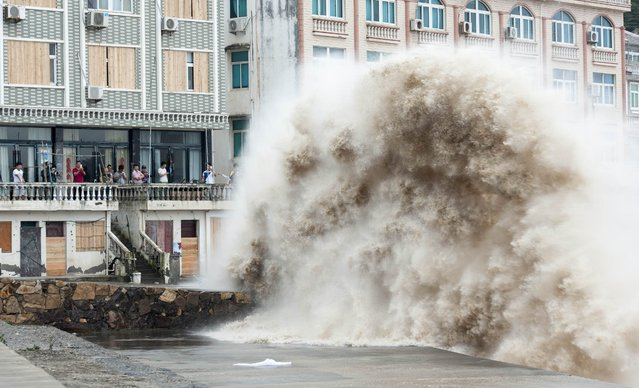 People gather to see huge waves as typhoon Chan-hom comes near Wenling, east China's Zhejiang province on July 10, 2015. (Photo by AFP Photo)