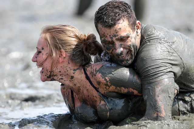 Partipants vie for the ball during the 11th Mud Olympics held at the North Sea coast in Brunsbuettel, Germany, July 11, 2015. Amateur athletes have competed in several disciplines  at the Mud Olympics since 2004. (Photo by Axel Heimken/EPA)