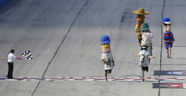 The Racing sausages take part in a race before the IndyCar Series race at the Milwaukee Mile in West Allis, Wis., Sunday, July 12, 2015. (Photo by Jeffrey Phelps/AP Photo)