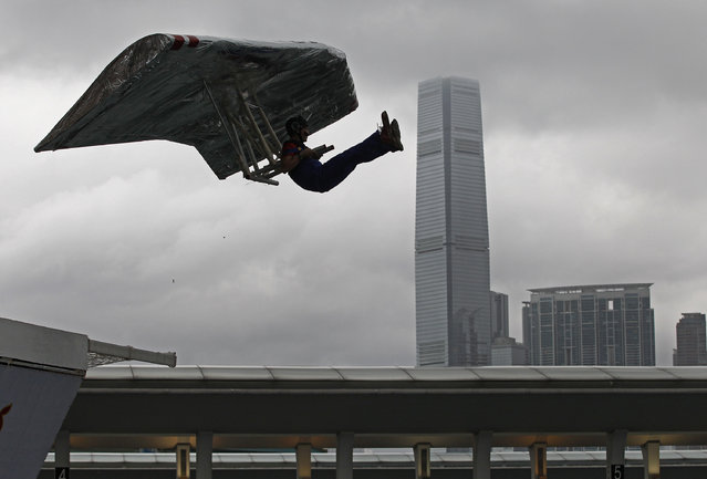 A participant sits in his self-made aircraft flying in front of the International Commerce Centre (ICC) at the Red Bull Flugtag (flight day) competition in Hong Kong, Sunday, May 11, 2014. Participants went into the air with home-made human-powered flying machines. (Photo by Vincent Yu/AP Photo)