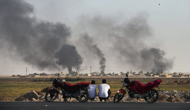 """People in Akcakale Sanliurfa province, southeastern Turkey, at the border with Syria, watch smoke billowing inside Syria, during bombardment by Turkish forces, Thursday, October 10, 2019. Turkey's foreign minister says Turkish troops intend to move some 30 kilometers (19 miles) deep into northern Syria and that its operation will last until all """"terrorists are neutralized"""", a reference to Syrian Kurdish fighters. (Photo by Emrah Gurel/AP Photo)"""