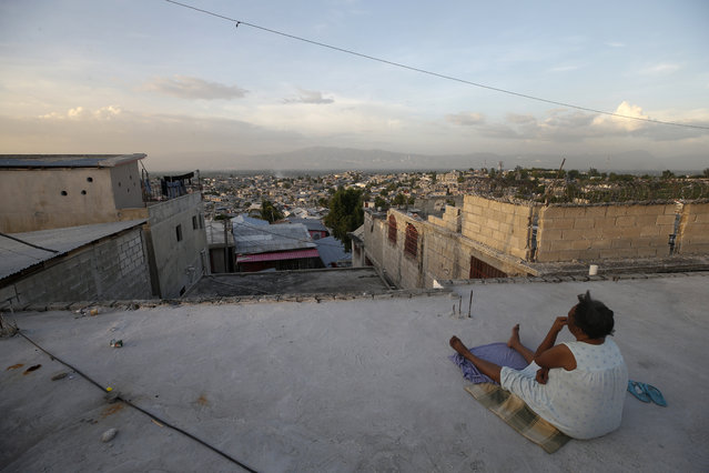 A woman rests on a rooftop in the Delmas neighborhood of Port-au-Prince, Haiti, Tuesday, October 8, 2019. (Photo by Rebecca Blackwell/AP Photo)