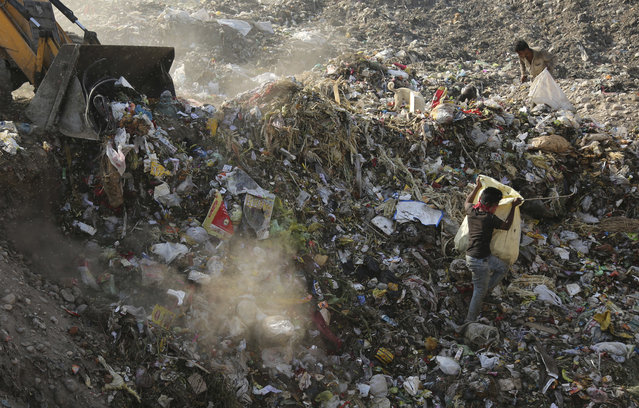 An excavator dumps garbage at a landfill on the outskirts of Jammu, India, Friday, April 21,2017. International Earth day falls on April 22. (Photo by Channi Anand/AP Photo)