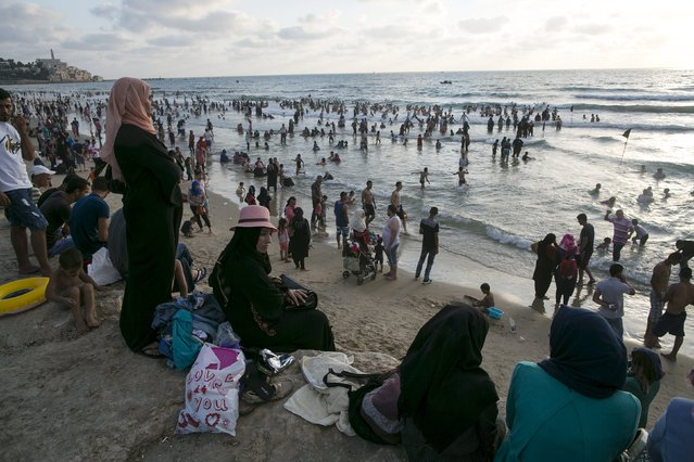 Muslim women watch people most from the West Bank and East Jerusalem in the water  of the Mediterranean in Tel Aviv during Eid al-Fitr, which marks the end of the holy month of Ramadan July 19, 2015. (Photo by Baz Ratner/Reuters)