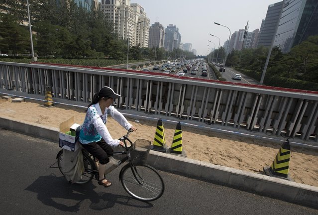 A woman rides past a city highway in Beijing, Sunday, July 12, 2015. Beijing's city government said Sunday that it is going to move part of its administrative functions out of the city center as part of a plan to better integrate the Chinese capital with its surrounding areas. (Photo by Andy Wong/AP Photo)