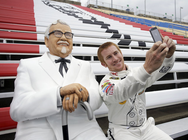 Front Row Motorsports driver Cole Whitt helps Kentucky Fried Chicken unveil Colonel Sanders as First-Ever Fan to secure  Seat for Life, at Kentucky Speedway  on Thursday, July 9, 2015 in Louisville, Ky. (Photo by Tony Tribble/Invision for KFC/AP Images)