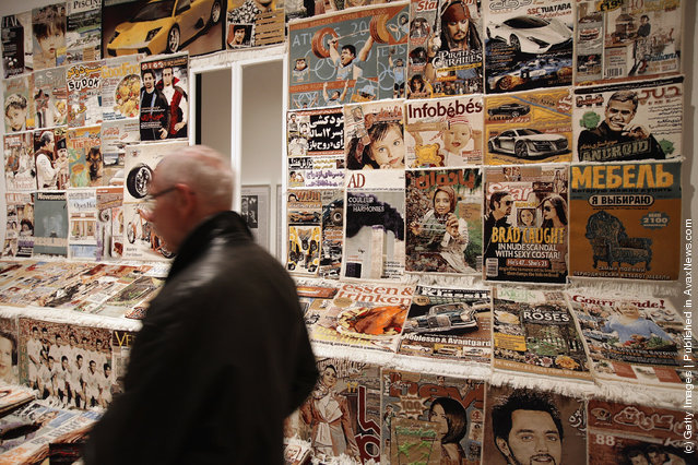 A visitor walks through an installation of carpets in the likeness of magazine covers by Iranian artist Fahrad Moshiri at the exhibition ARTandPRESS at Martin Gropius Bau