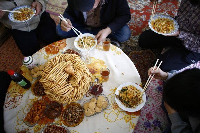 Uighur refugees have their lunch in a gated complex where they are housed in the central city of Kayseri, Turkey, February 11, 2015. Thousands of members of China's Turkic language-speaking Muslim ethnic minority have reached Turkey, mostly since last year, infuriating Beijing, which accuses Ankara of helping its citizens flee unlawfully. Turkish officials deny playing any direct role in assisting the flight. (Photo by Umit Bektas/Reuters)
