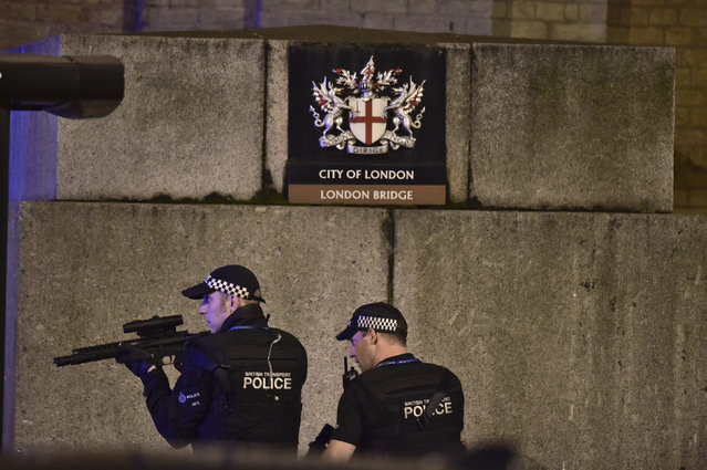 """An armed Police officer looks through his weapon on London Bridge in London, Saturday, June 3, 2017.  British police said they were dealing with """"incidents"""" on London Bridge and nearby Borough Market in the heart of the British capital Saturday, as witnesses reported a vehicle veering off the road and hitting several pedestrians. (Photo by Dominic Lipinski/PA Wire via AP Photo)"""