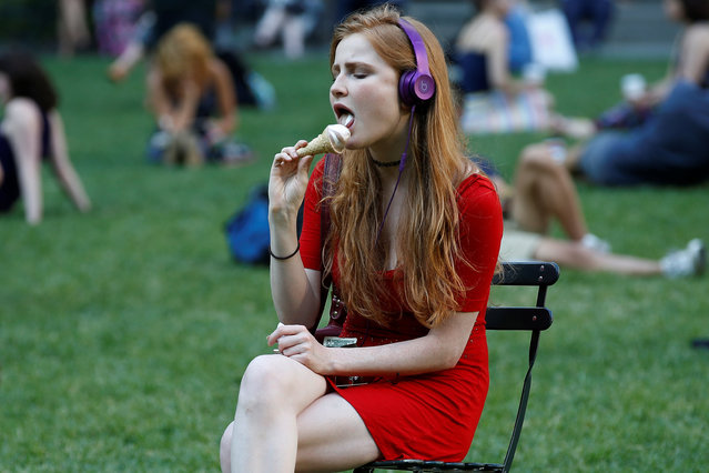 A woman eats an ice-cream cone in Bryant Park in the Manhattan borough of New York, U.S., May 31, 2016. (Photo by Carlo Allegri/Reuters)