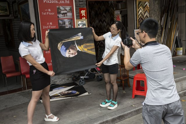 "Salespeople roll out a reproduction of the famous work ""Girl with a Pearl Earring"" at the artist village on June 11, 2014 in Shenzhen, China. The Dafen Artist Village in Guangdong province, China, is home to thousands of artists who reproduce some of the world's most iconic paintings as well as create their own works. The village, on the outskirts of Shenzhen, is becoming a major center for original Chinese art. (Photo by Palani Mohan/Getty images)"