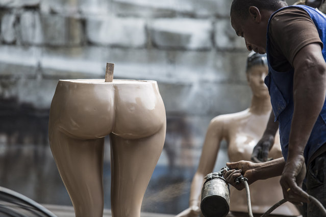 The manufacturers are independent and work in informal street shops by the roads of Abidjan. Many began by moulding cement or plastic plant pots but as an influx of cheap clothing has come into the city, the demand for mannequins has increased. Here: An Awoulaba mannequin being sprayed. (Photo by Joana Choumali)