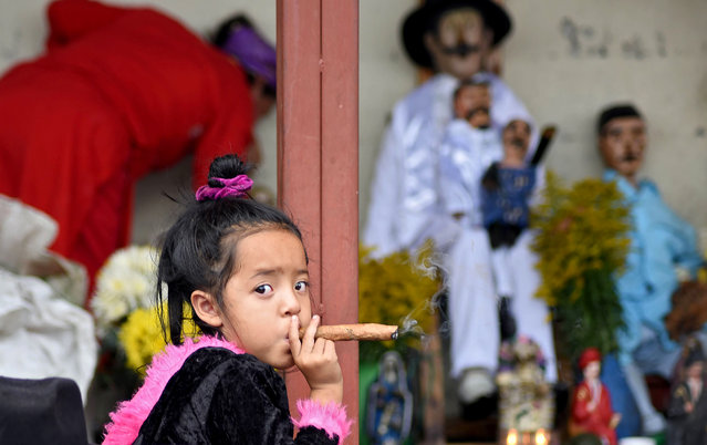 A three-year-old girl smokes a cigar during the Saint Simon celebrations in San Andres Itzapa, Guatemala, on October 28, 2019. Thousands believe that the saint helps people find work, solves family problems and cures illnesses. (Photo by Orlando Estrada/AFP Photo)