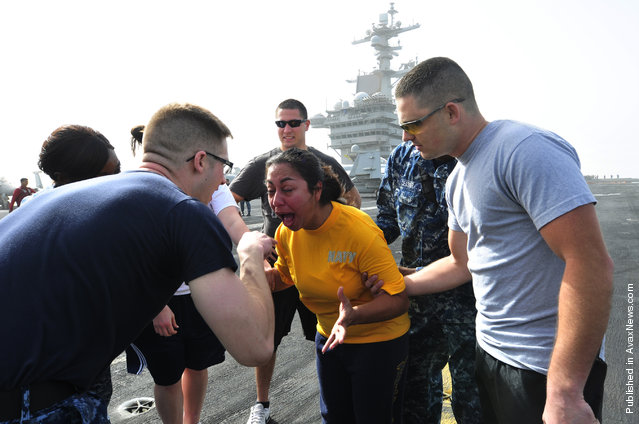 Master-at-Arms 2nd Class Jonathan Prichard instructs Operations Specialist 3rd Class Gladys Jerezrendon, to open her eyes after being sprayed with oleoresin capsicum (OC) spray during a security academy OC spray qualification on the flight deck aboard the Nimitz-class aircraft carrier USS Carl Vinson (CVN 70)