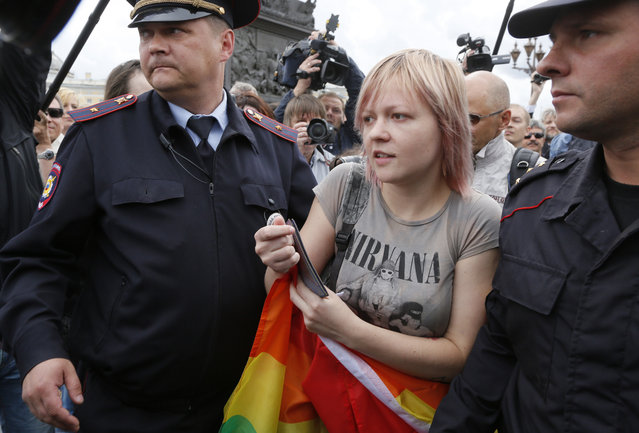 Police officers detain a gay rights activist standing with a rainbow flag during a protest at Dvortsovaya (Palace) Square in St.Petersburg, Russia, Sunday, August 2, 2015. (Photo by Dmitry Lovetsky/AP Photo)