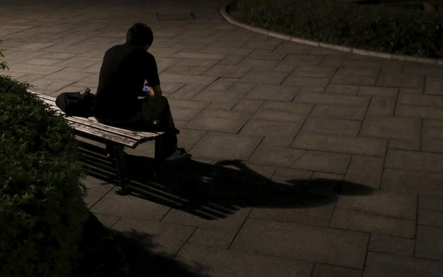 A man casts a shadow on the ground as he sits on a bench near a street light at night near the Atomic Bomb Dome in Hiroshima, western Japan July 27, 2015. (Photo by Issei Kato/Reuters)