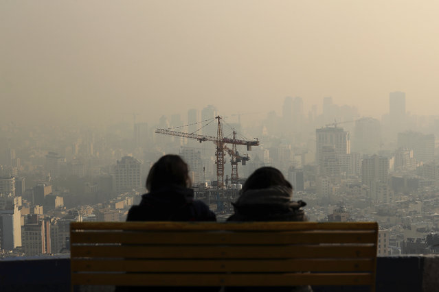 People look at the skyline through polluted air, in the Velenjak mountainous area of Tehran, Iran Monday, December 23, 2019. Dangerously poor air quality forced Iran's government on Monday to keep all schools closed in the capital, Tehran, and other cities. Schools were closed since Saturday, and will remain closed until Wednesday, the end of the week in Iran, according to the official IRNA news agency. Tehran's air is among the most polluted in the world. (Photo by Ebrahim Noroozi/AP Photo)