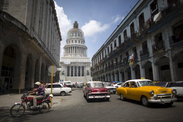 Cuba's Capitol, or El Capitolio as it is called by Cubans (rear), is seen in Havana, July 9, 2015. Cubans are once again touring their Capitol, an imposing structure previously shunned as a symbol of U.S. imperialism but now undergoing renovation and set to reopen as the new home of the Communist government's National Assembly. (Photo by Alexandre Meneghini/Reuters)