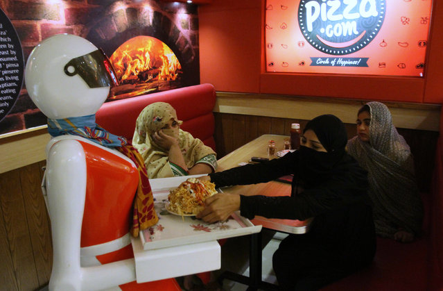 A robot waitress serves food to customers at a pizza restaurant in Multan, Pakistan, Thursday, July 6, 2017. A Pakistani engineer says sale of Pizza at his father's shop has doubled in recent months after he introduced first ever robot to serve food to customers in the central city of Multan. (Photo by Iram Asim/AP Photo)
