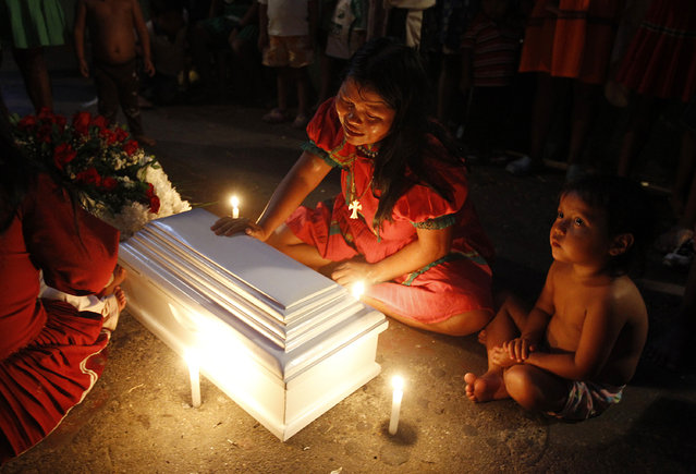 Luz Elaida Queragama, an indigenous Embera Katio, cries beside the coffin of her four-month-old daughter who died in Cali January 25, 2015. Queragama discovered that her baby was not breathing. Members of the displaced Katio community came to Cali in 2013 following an armed conflict that was raging in Pueblo Rico, Risaralda. They now live in poverty in Cali, in three houses that are inhabited by 43 families, authorities said. (Photo by Jaime Saldarriaga/Reuters)