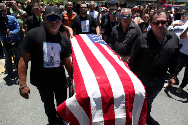 Family and friends carry the coffin of Angel Candelario, one of the victims of the shooting at the Pulse night club in Orlando, covered with a Puerto Rico flag during his funeral at his hometown of Guanica, Puerto Rico, June 18, 2016. (Photo by Alvin Baez/Reuters)