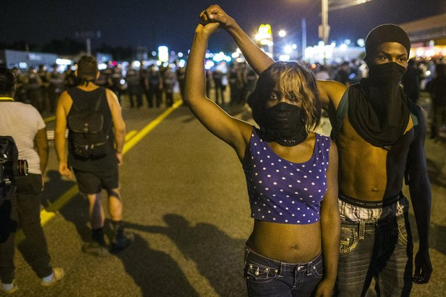 Two anti-police demonstrators walk away from a line of St Louis County police officers during protests in Ferguson, Missouri August 11, 2015. Police in riot gear clashed with protesters who had gathered in the streets of Ferguson early on Tuesday to mark the anniversary of the police shooting of an unarmed black teen whose death sparked a national outcry over race relations. REUTERS/Lucas Jackson
