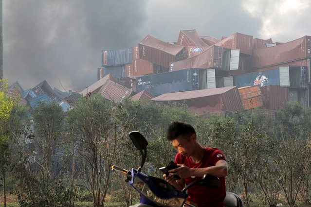 A man checks his mobile phone near overturned shipping containers after explosions hit the Binhai new district, Tianjin, August 13, 2015. (Photo by Reuters/Stringer)