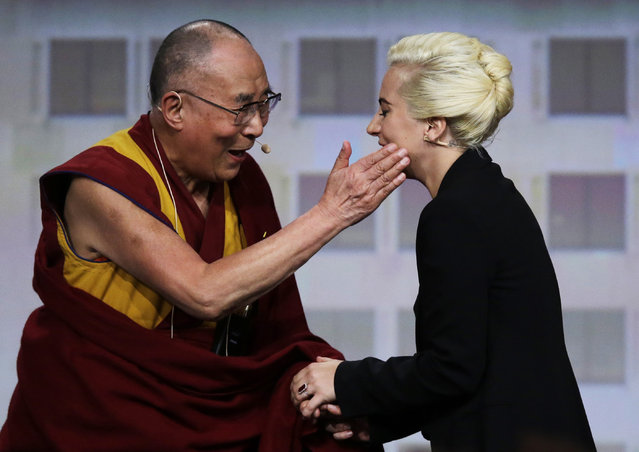 The Dalai Lama greets Lady Gaga, right, before a question and answer session at the U.S. Conference of Mayors in Indianapolis, Sunday, June 26, 2016. (Photo by Michael Conroy/AP Photo)